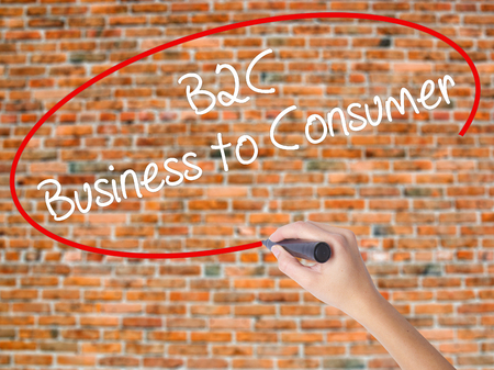 Woman Hand Writing B2C Business to Consumer with black marker on visual screen. Isolated on bricks. Business concept. Stock Photo Stock Photo