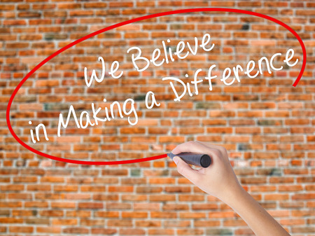 Woman Hand Writing We Believe in Making a Difference with black marker on visual screen. Isolated on bricks. Business concept. Stock Photo