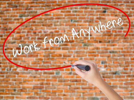 homeoffice: Woman Hand Writing Work from Anywhere with black marker on visual screen. Isolated on bricks. Business concept. Stock Photo