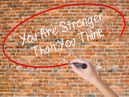 Woman Hand Writing You Are Stronger Than You Think with black marker on visual screen. Isolated on bricks. Business concept. Stock Photo