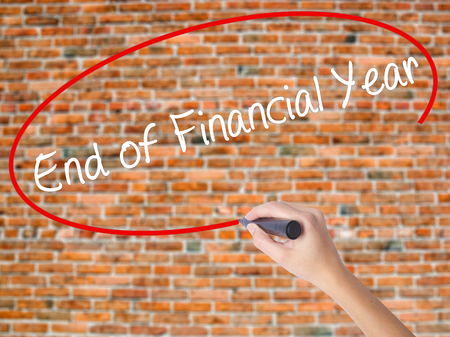 Woman Hand Writing End of Financial Year with black marker on visual screen. Isolated on bricks. Business concept. Stock Photo