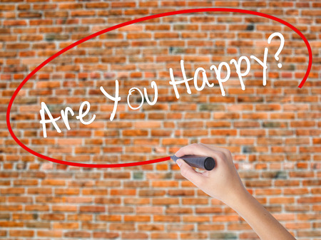 properous: Woman Hand Writing Are You Happy? with black marker on visual screen. Isolated on bricks. Business, technology, internet concept.