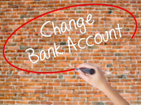 Woman Hand Writing Change Bank Account with black marker on visual screen. Isolated on bricks. Business concept. Stock Photo