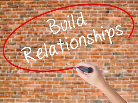 Woman Hand Writing Build Relationships with black marker on visual screen. Isolated on bricks. Business concept. Stock Photo Stock Photo