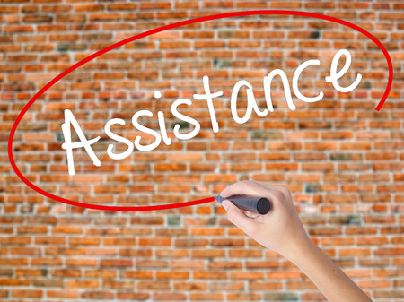 Woman Hand Writing Assistance with black marker on visual screen. Isolated on bricks. Business concept. Stock Photo