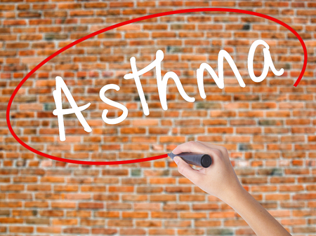 Woman Hand Writing Asthma with black marker on visual screen. Isolated on bricks. Business concept. Stock Photo Stock Photo