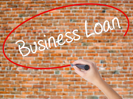 Woman Hand Writing Business Loan with black marker on visual screen. Isolated on bricks. Business concept. Stock Photo
