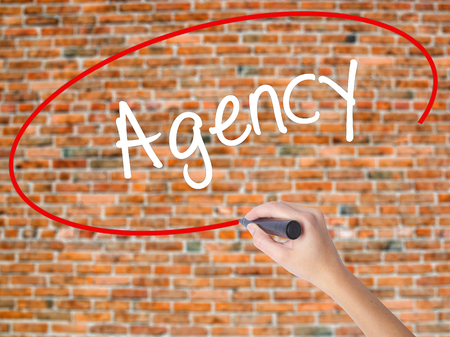 Woman Hand Writing Agency with black marker on visual screen. Isolated on bricks. Business concept. Stock Photo Stock Photo