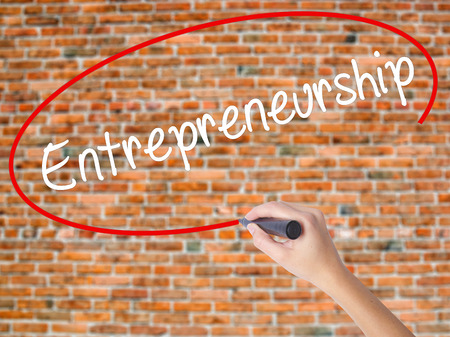 Woman Hand Writing Entrepreneurship with black marker on visual screen. Isolated on bricks. Business concept. Stock Photo Stock Photo