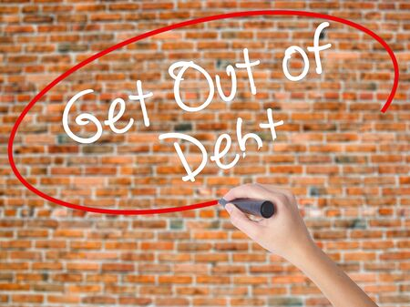 Woman Hand Writing Get Out of Debt with black marker on visual screen. Isolated on bricks. Business concept. Stock Photo