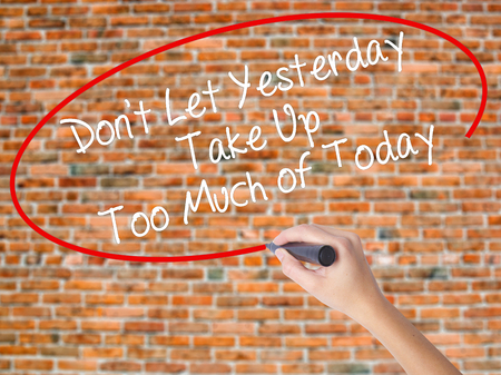 street wise: Woman Hand Writing Dont Let Yesterday Take Up Too Much of Today with black marker on visual screen. Isolated on bricks. Business concept. Stock Photo Stock Photo