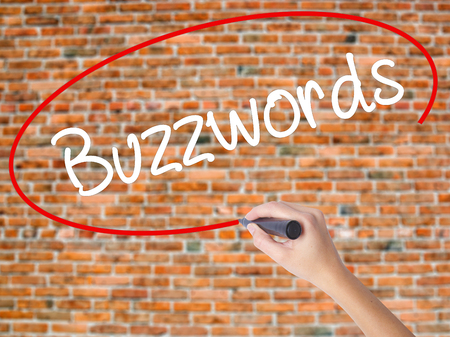 Woman Hand Writing Buzzwords with black marker on visual screen. Isolated on bricks. Business concept. Stock Photo Stock Photo