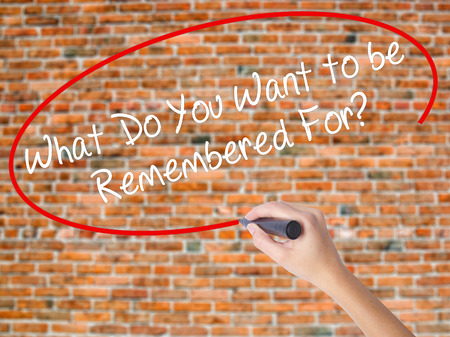 egoista: Woman Hand Writing What Do You Want to be Remembered For? with black marker on visual screen. Isolated on bricks. Business concept. Stock Photo