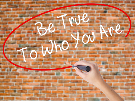 Woman Hand Writing Be True To Who You Are with black marker on visual screen. Isolated on bricks. Business concept. Stock Photo