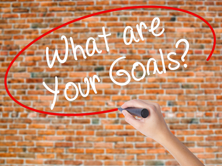 supervisión: Woman Hand Writing What are Your Goals?  with black marker on visual screen. Isolated on bricks. Business concept. Stock Photo