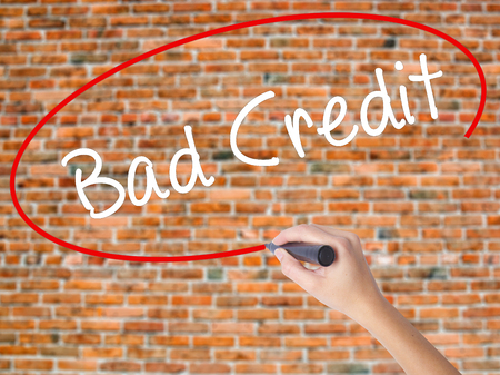 Woman Hand Writing Bad Credit with black marker on visual screen. Isolated on bricks. Business concept. Stock Photo