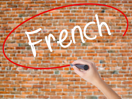 Woman Hand Writing French with black marker on visual screen. Isolated on bricks. Business concept. Stock Photo