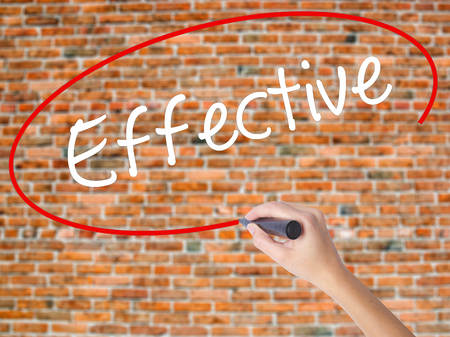 Woman Hand Writing Effective with black marker on visual screen. Isolated on bricks. Business concept. Stock Photo
