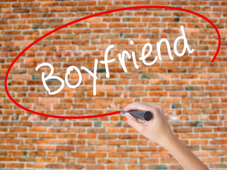 Woman Hand Writing Boyfriend with black marker on visual screen. Isolated on bricks. Business concept. Stock Photo