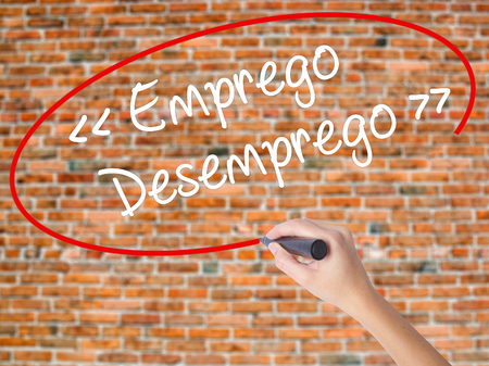 challenges ahead: Woman Hand Writing Emprego Desemprego (Employment - Unemployment in Portuguese)  with black marker on visual screen. Isolated on bricks. Business concept. Stock Photo Stock Photo