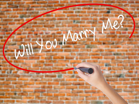 Woman Hand Writing Will You Marry Me? with black marker on visual screen. Isolated on bricks. Business concept. Stock Photo
