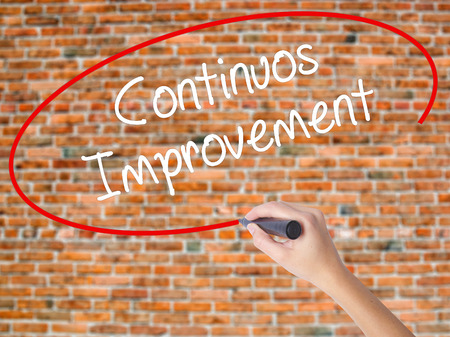 Woman Hand Writing Continuos Improvement with black marker on visual screen. Isolated on bricks. Business concept. Stock Photo