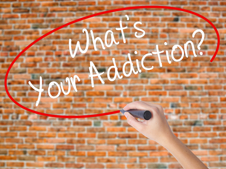 narcotic: Woman Hand Writing Whats your Addiction? with black marker on visual screen. Isolated on bricks. Business concept. Stock Photo