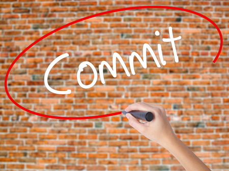 Woman Hand Writing Commit with black marker on visual screen. Isolated on bricks. Business concept. Stock Photo