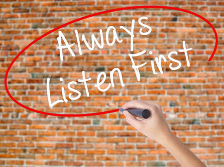 Woman Hand Writing Always Listen First with black marker on visual screen. Isolated on bricks. Business concept. Stock Photo Stock Photo