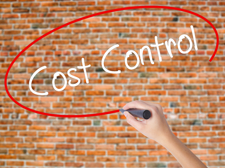 Woman Hand Writing Cost Control with black marker on visual screen. Isolated on bricks. Business,  internet concept. Stock Photo