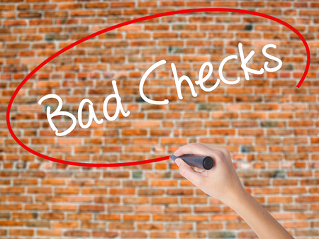 Woman Hand Writing Bad Checks with black marker on visual screen. Isolated on bricks. Business concept. Stock Photo