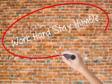 Woman Hand Writing Work Hard Stay Humble  with black marker on visual screen. Isolated on bricks. Business, technology, internet concept. Stock Photo