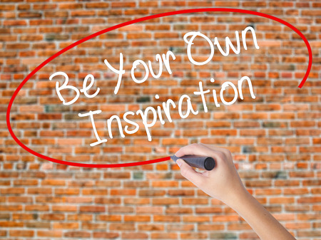 owning: Woman Hand Writing Be Your Own Inspiration with black marker on visual screen. Isolated on bricks. Business concept. Stock Photo