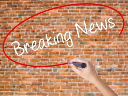 Woman Hand Writing Breaking News with black marker on visual screen. Isolated on bricks. Business concept. Stock Photo