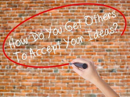 Woman Hand Writing How Do You Get Others To Accept Your Ideas? with black marker on visual screen. Isolated on bricks. Business concept. Stock Photo