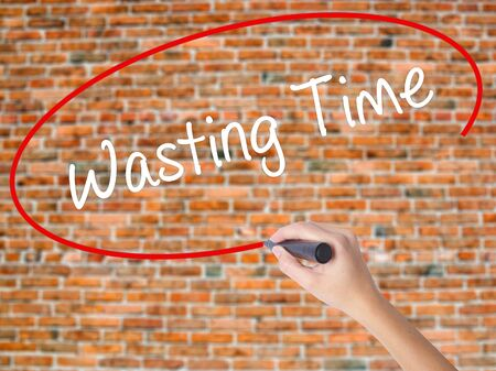 Woman Hand Writing Wasting Time with black marker on visual screen. Isolated on bricks. Business, technology, internet concept. Stock Photo
