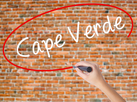 Woman Hand Writing Cape Verde with black marker on visual screen. Isolated on bricks. Business concept. Stock Photo