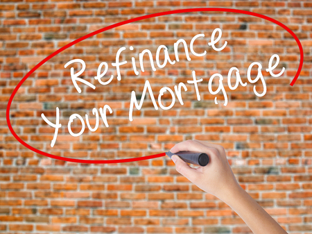 Woman Hand Writing Refinance Your Mortgage with black marker on visual screen. Isolated on bricks. Business concept. Stock Photo Stock Photo