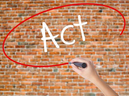 Woman Hand Writing Act  with black marker on visual screen. Isolated on bricks. Business concept. Stock Photo