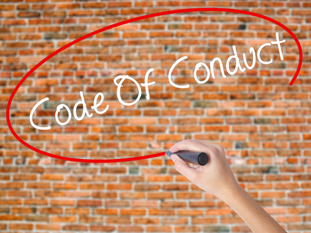 Woman Hand Writing Code Of Conduct with black marker on visual screen. Isolated on bricks. Business concept. Stock Photo