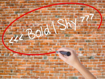 bashful: Woman Hand Writing Bold - Shy  with black marker on visual screen. Isolated on bricks. Business concept. Stock Photo