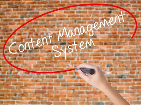 Woman Hand Writing Content Management System  with black marker on visual screen. Isolated on bricks. Business concept. Stock Photo Stock Photo