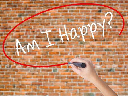 Woman Hand Writing Am I Happy? with black marker on visual screen. Isolated on bricks. Business concept. Stock Photo