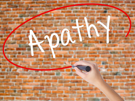 Woman Hand Writing Apathy  with black marker on visual screen. Isolated on bricks. Business concept. Stock Photo Stock Photo