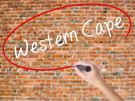 Woman Hand Writing Western Cape with black marker on visual screen. Isolated on bricks. Business concept. Stock Photo Stock Photo