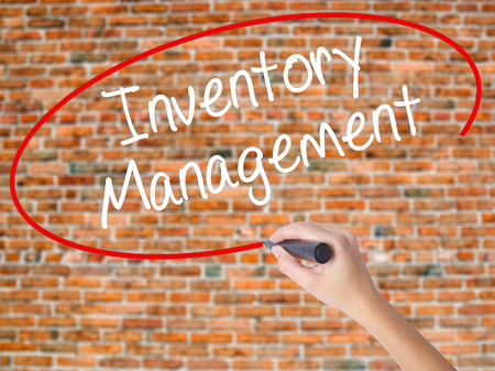 manufacturer: Woman Hand Writing Inventory Management with black marker on visual screen. Isolated on bricks. Business concept. Stock Photo