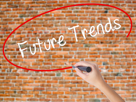 Woman Hand Writing Future Trends with black marker on visual screen. Isolated on bricks. Business, technology, internet concept.