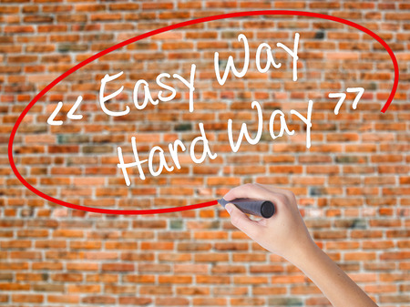 Woman Hand Writing Easy Way - Hard Way with black marker on visual screen. Isolated on bricks. Business concept. Stock Photo