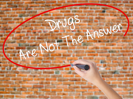 Woman Hand Writing Drugs Are Not The Answer with black marker on visual screen. Isolated on bricks. Business concept. Stock Photo