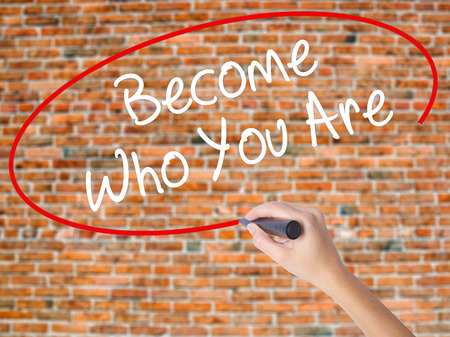Woman Hand Writing Become Who You Are with black marker on visual screen. Isolated on bricks. Business concept. Stock Photo Stock Photo